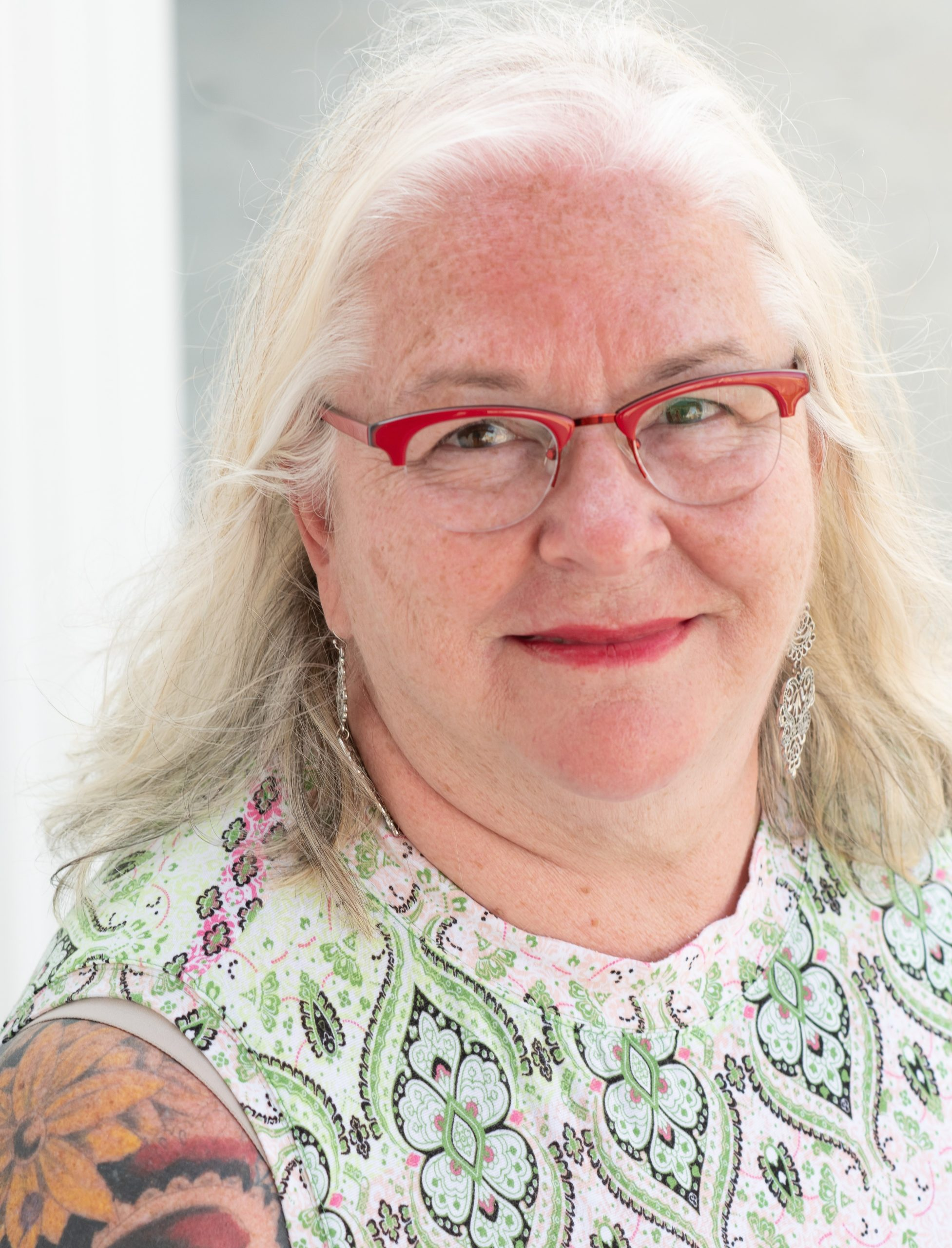 Deb Brown, a white woman with long white hair, poses in front of a light background, wearing red glasses, red lipstick, and a green and white printed sleeveless top