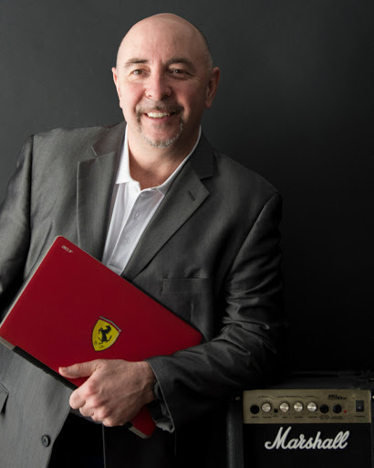 Gair Maxwell, a white man with a dark goatee and moustache, stands in front of a dark background in a grey suit and light shirt, leaning on a Maxwell amp and holding a Porsche folder