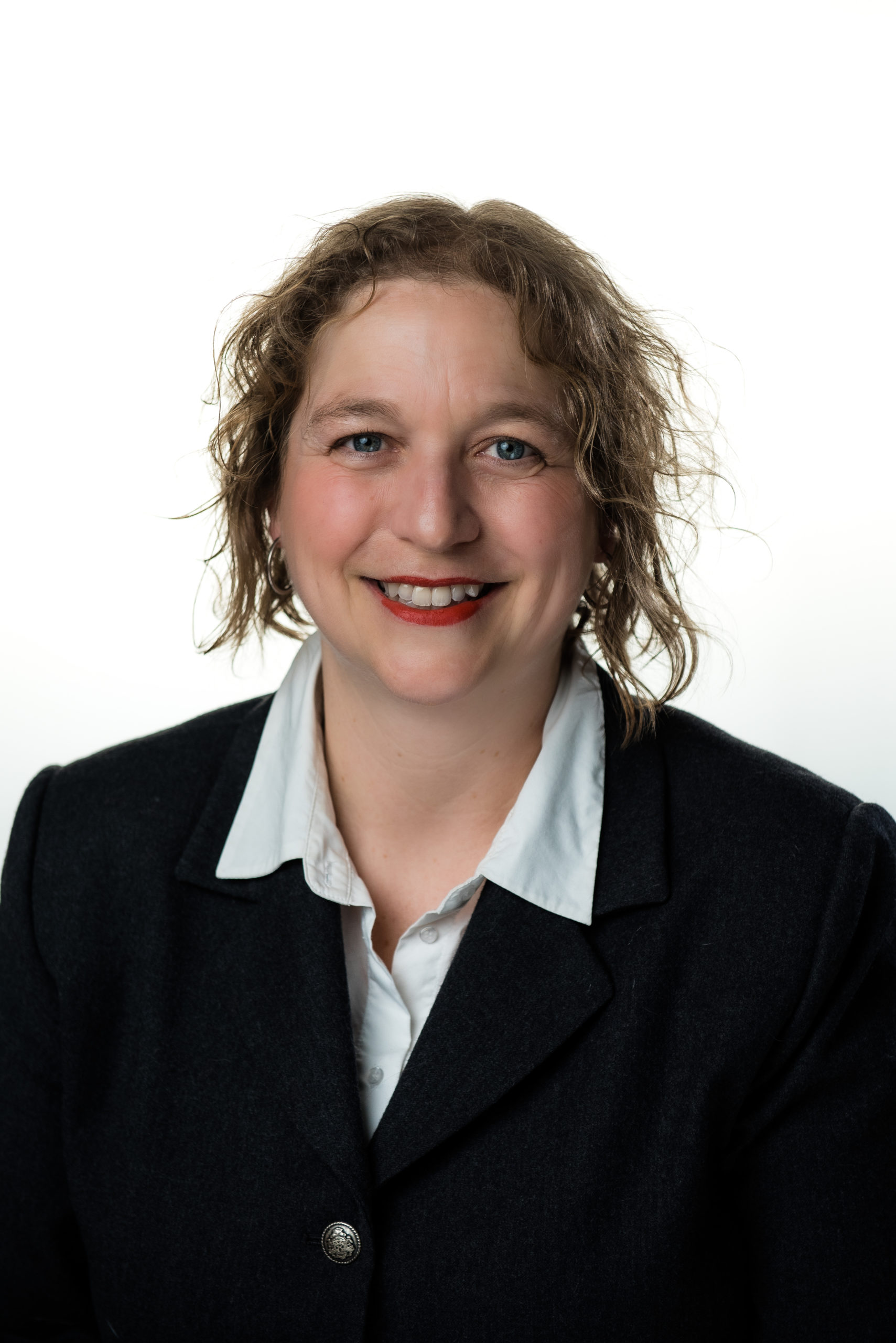 Meredity Maywood, a white woman with wavy light brown hair, sits in front of a white background, wearing a black suit jacket and light blue shirt
