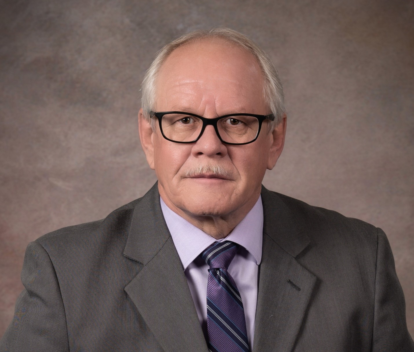 Ron McCullough, a white man with white hair on the sides and a white moustache, sits in front of a mottled brown background, wearing black glasses, a grey suit, a purple shirt, and a patterned purple tie